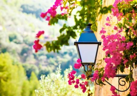 Street lantern with flowers in Deia village, Mallorca, Baleares, Spain photo