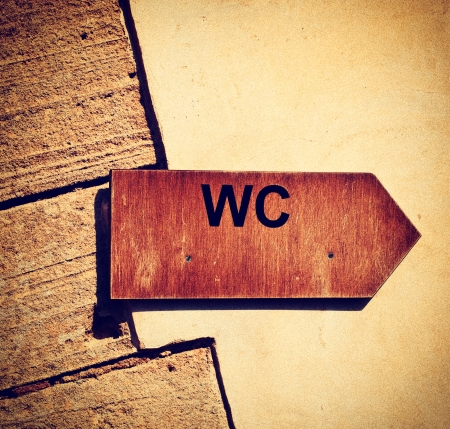 excrete: Toilet wooden sign pointer in vintage style Stock Photo