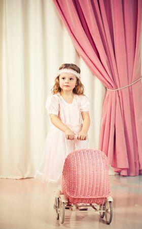 Little beautiful girl play with pram photo