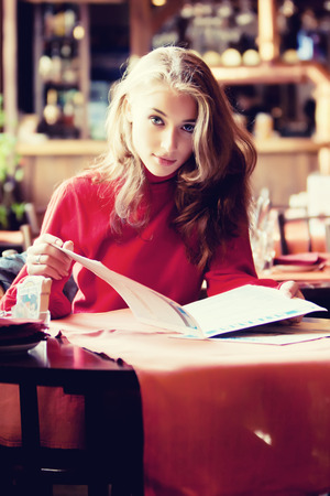Beautiful woman with menu in cafe photo