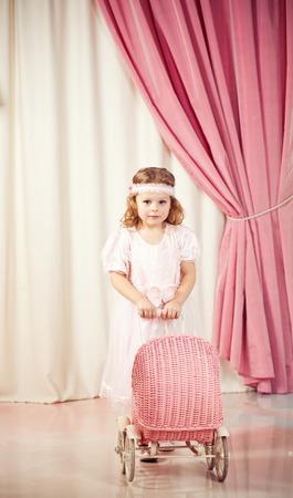 niño empujando: Juego Pequeña muchacha hermosa con el cochecito de niño