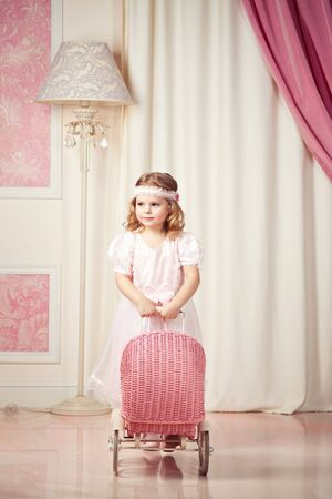 courtain: Little beautiful girl game with pram Stock Photo