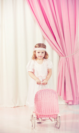 courtain: Little beautiful girl play with pram Stock Photo