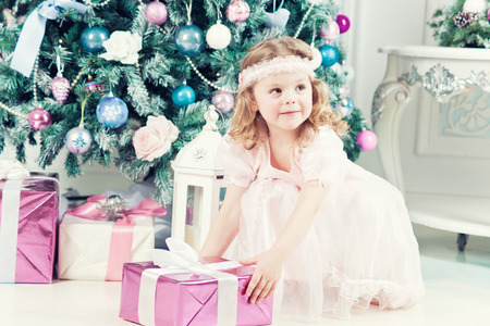 Beautiful little girl with christmas tree and gifts photo