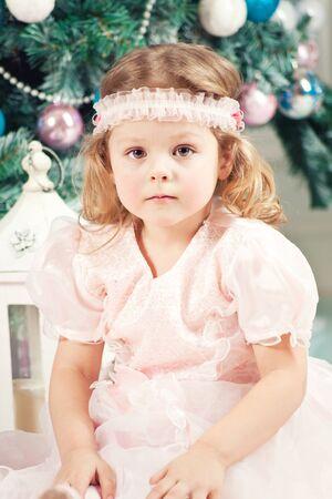 Beautiful little girl with christmas tree photo