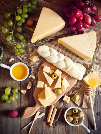 Cheese plate with various cheeses, grape and honey