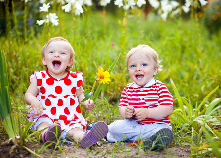 babies playing: Happy twins boy and girl on summer park Stock Photo