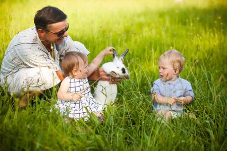 grandad: Grandfather with twins grandchildren and white rabbit outdor