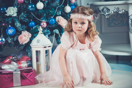 Little girl in beautiful dress with christmas tree photo