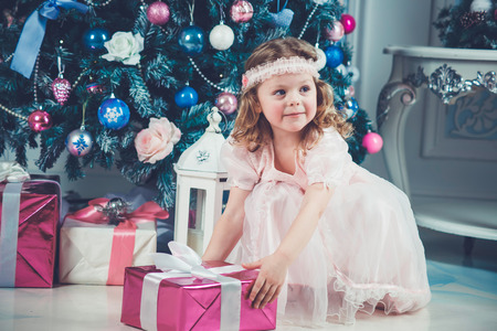 Little girl in beautiful dress with christmas tree and gift photo