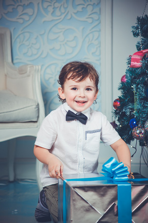 Happy boy with christmas tree and gift photo