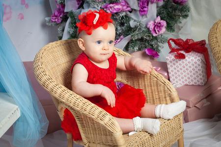 Pequeño bebé con el árbol de Navidad y regalos