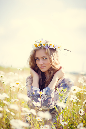 Beautiful girl with circlet of flowers in summer chamomile field Stock Photo