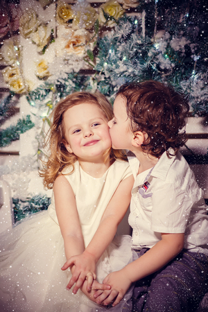 Little boy kissing a girl im christmas photo