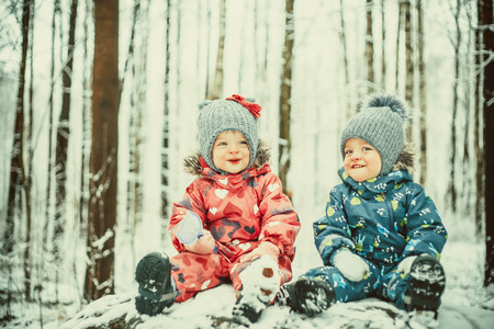Happy twin kids boy and girl in winter snowy winter park photo
