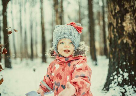 Beautiful little girl in snowy winter park photo