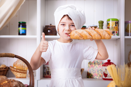 Funny little cook in kitchen with bakery photo