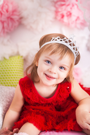Cute little princess on pink bed photo