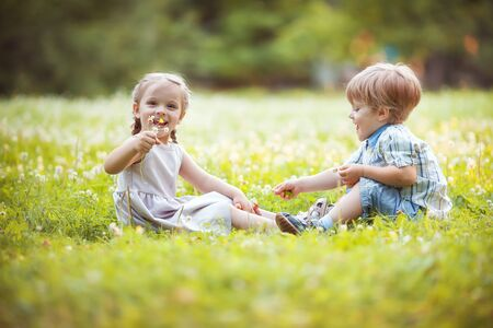 Funny little twins boy and girl in summer park Stockfoto - 133384756