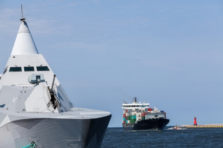 Container ship and the  stealth warship at the entrance to the port of Gdansk  photo