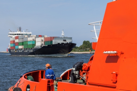 Tug boat helps the port entrance container ship  photo