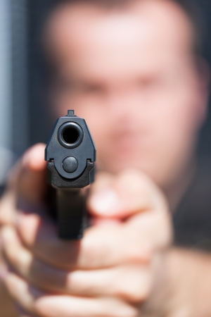 男から銃の銃のバレルに焦点を当てることを目指しています 写真素材