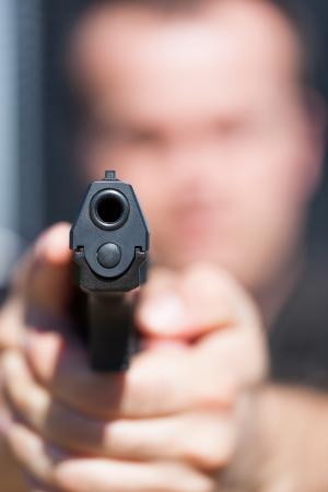 Der Mann soll aus der Pistole Fokus auf Barrel Gun Standard-Bild - 21015159
