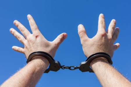 wristlets: Man hands with handcuffs on blue background