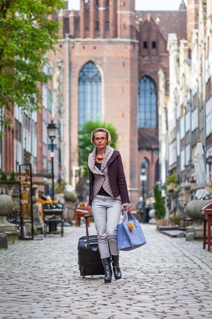 Blonde woman with baggage on the historic street  photo