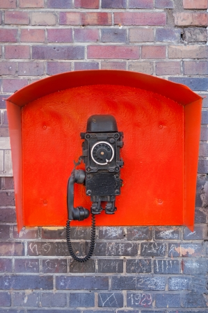 Old industrial telephone hanging on the wall  photo