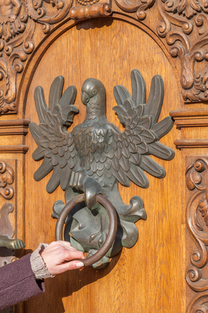 Female hand on the vintage door knocker  photo