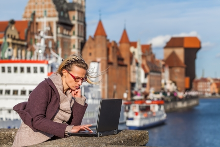 Girl with laptop on the background old town in Gdansk