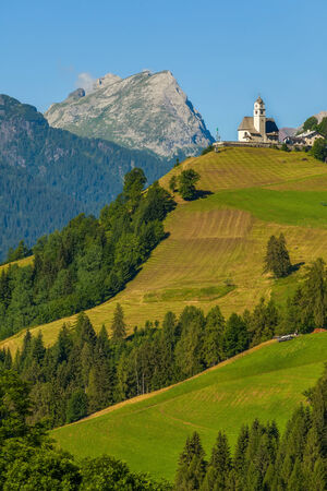 Church with clock tower on a  mountains photo