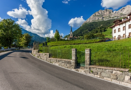 Roadside church with the clock tower in the town at the foot of the Dolomites photo