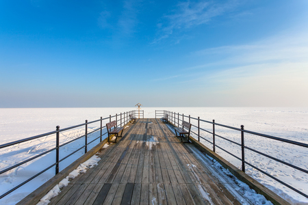 Frozen sea and wooden pier at sunset photo