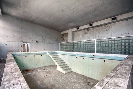 Forgotten, old swimming pool in a ruined building photo