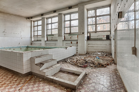 Forgotten, old swimming pool in a ruined building Stock Photo