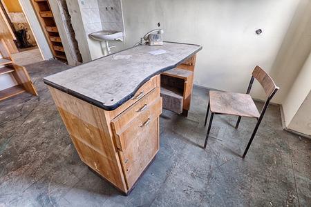 放棄された病院中古い机といす 写真素材