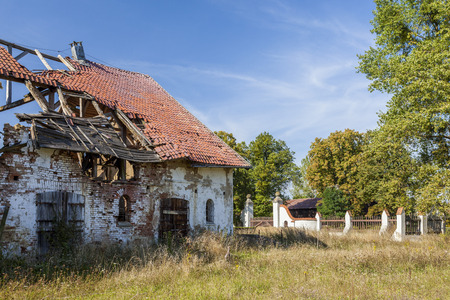 damaged roof: Overgrown ruins of an old manor house Stock Photo