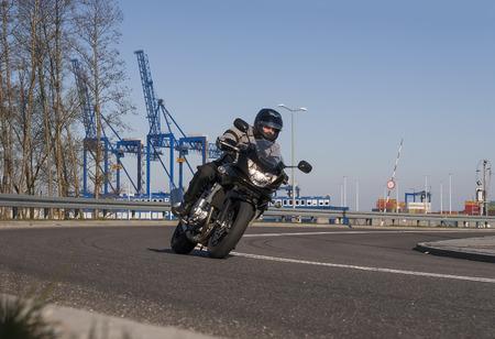 道路の曲がり角にモーターサイク リスト 写真素材