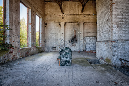 Armchair in the middle of an abandoned warehouse