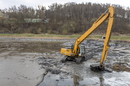 Excavator working at deepening the pond Banco de Imagens