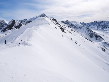 Skier on the slope and peaks of the mountains in the background Banco de Imagens