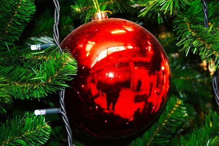 Red ball hanging on a Christmas tree near the lights of a garland