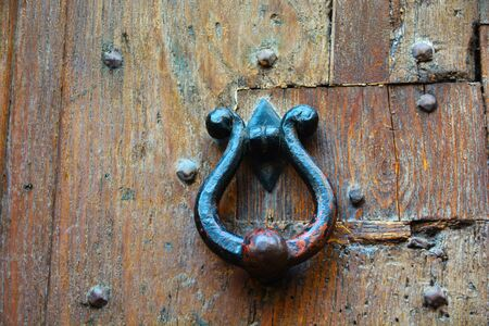 Round knocker on an old wooden entrance door 写真素材