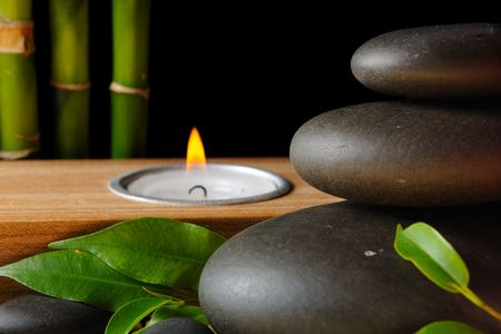 Bamboo,zen stones and candlestck on the black background photo