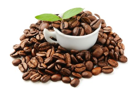 white cup with  coffee beans and leaves photo