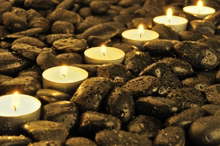black pebbles: several burning candle on the wet stones