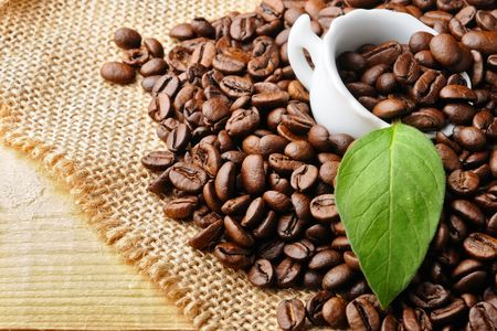 white cup with  coffee and coffee beans