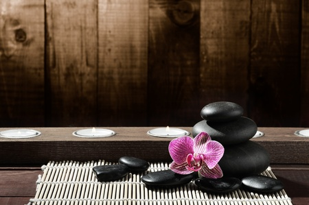 hot rock therapy: zen black stones and pink orchid Stock Photo